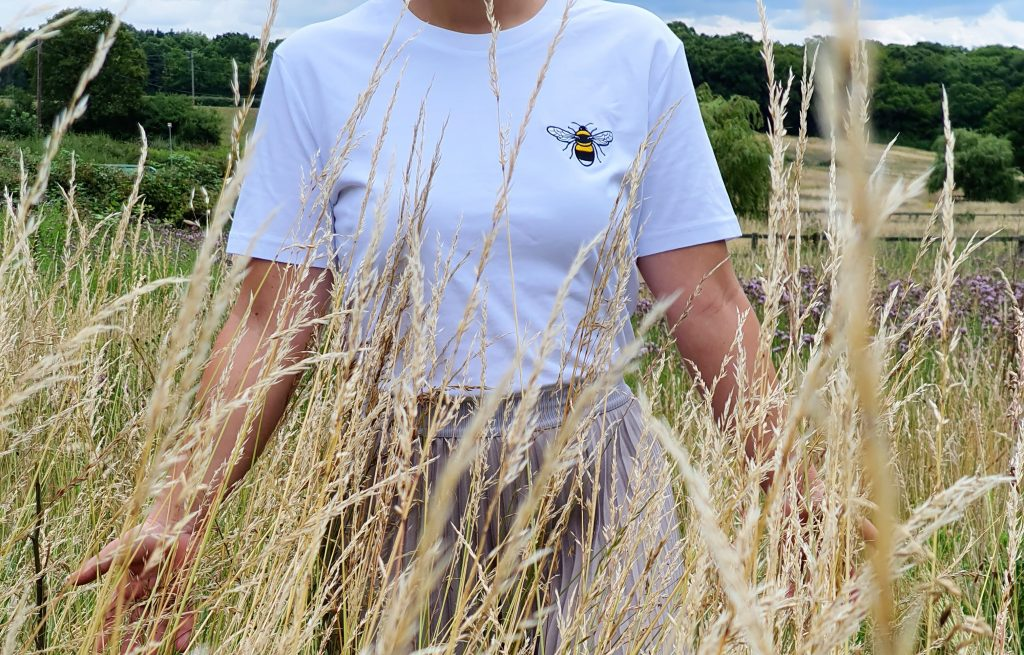 Amelie from Maplantic wearing a tommy and lottie organic cotton embroidered bee t shirt in a wildlife field